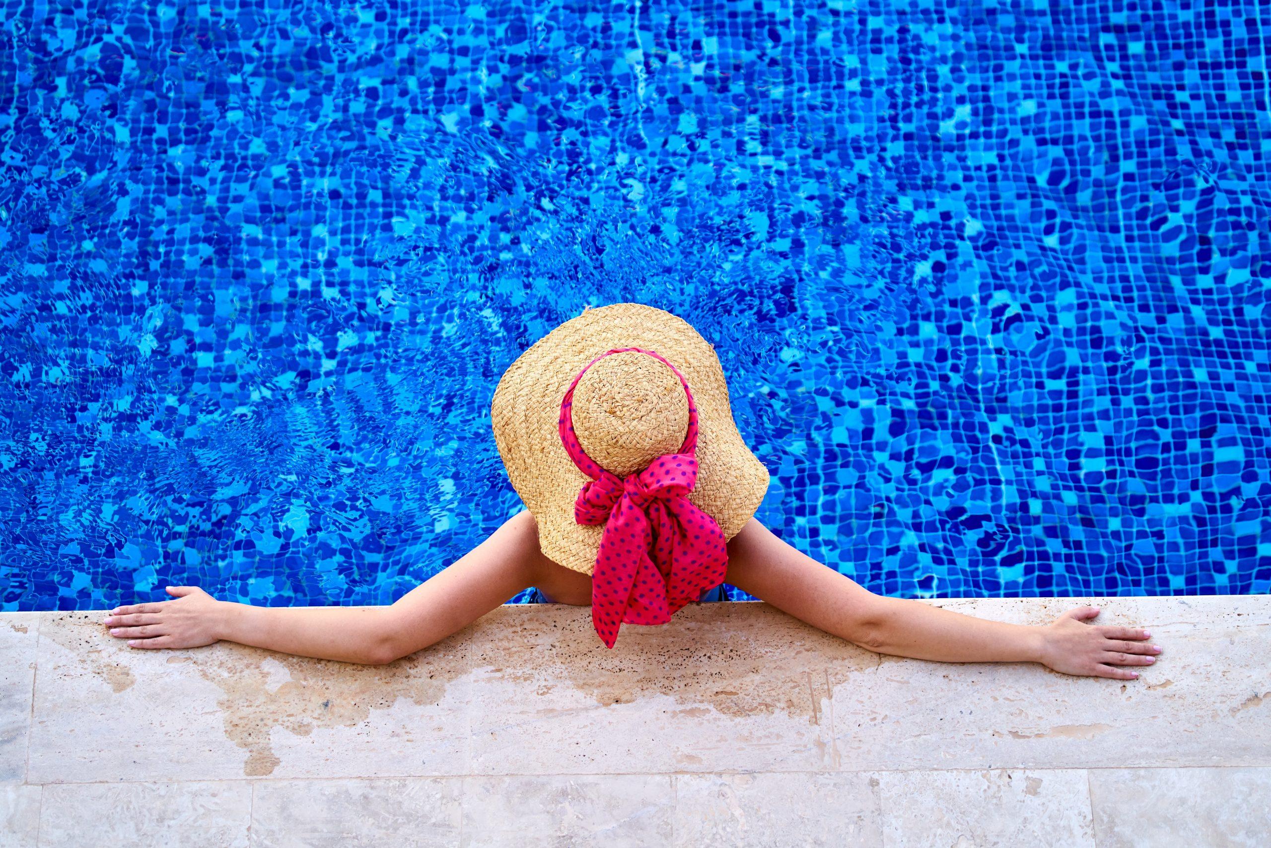 donna con cappello di paglia fiocco rosso in piscina
